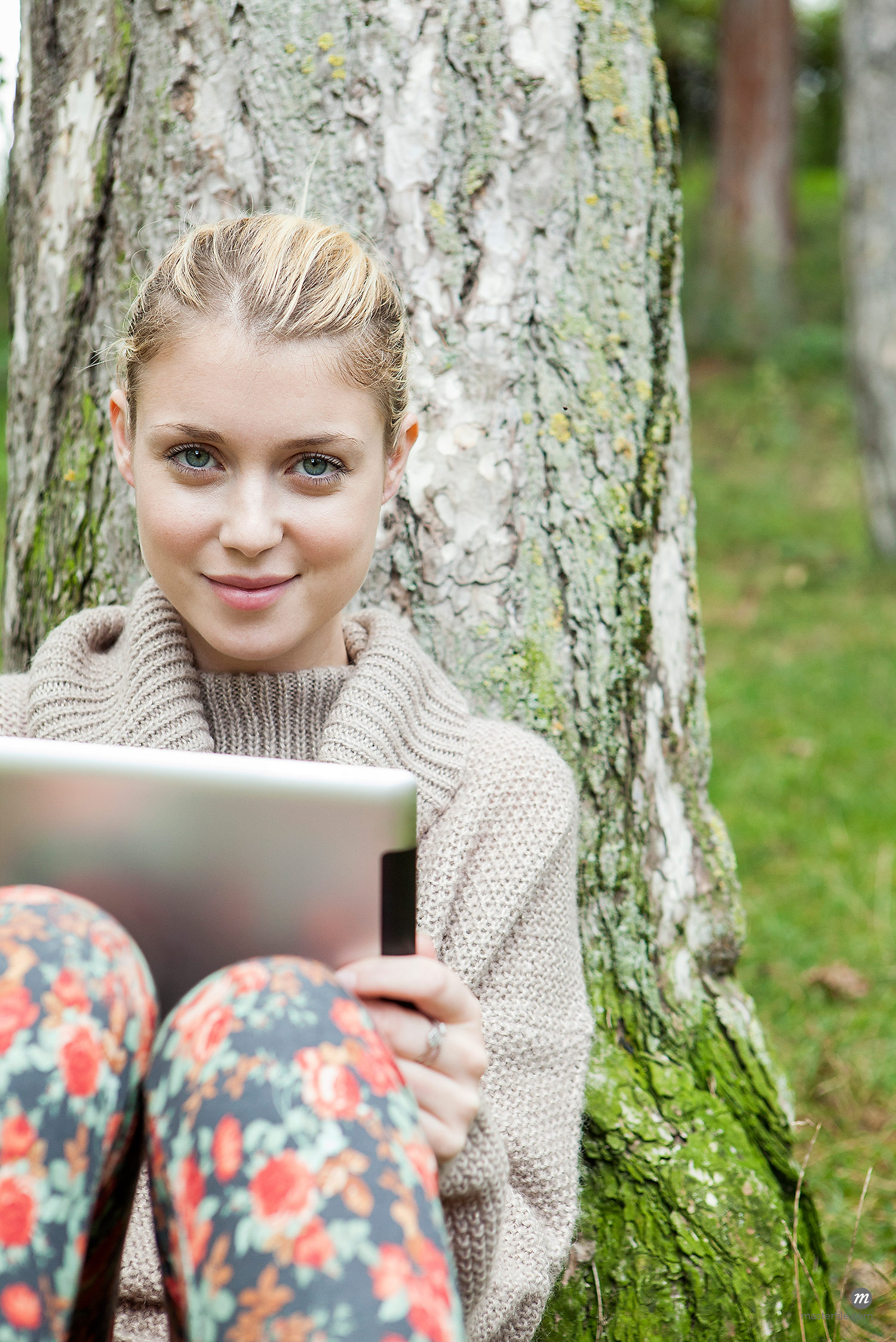Woman outdoors leaning against tree using digital tablet  © Masterfile