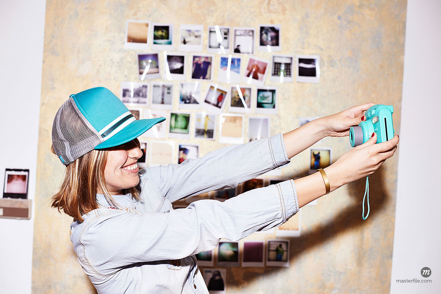 Young woman in front of photo wall taking instant selfie  © Masterfile
