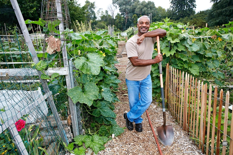 Black man leaning on shovel in community garden  © Masterfile