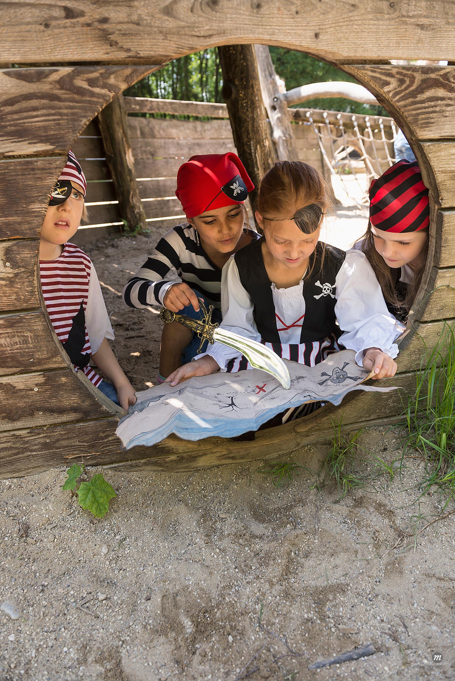 Girls dressed up as pirates watching a treasure map in adventure playground  © Masterfile