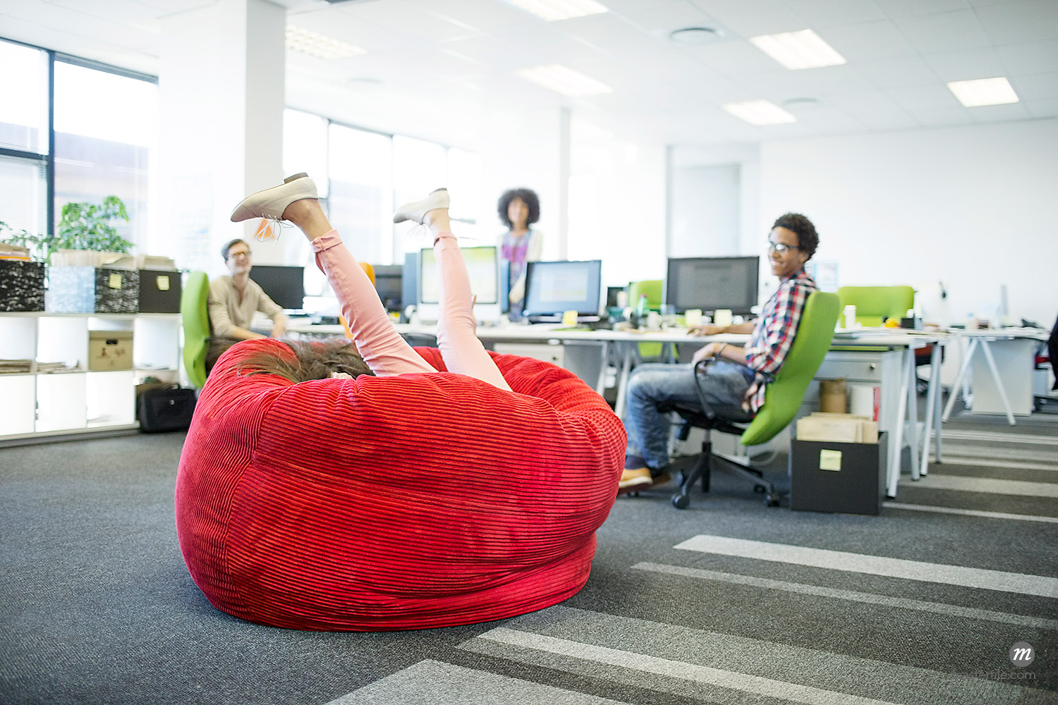 Businesswoman playing in beanbag chair in open concept office  © Masterfile