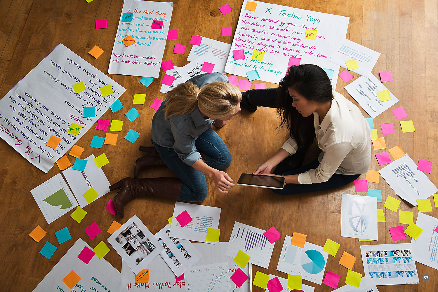 Colleagues with tablet sitting on floor surrounded by paper and colourful notes  © Masterfile
