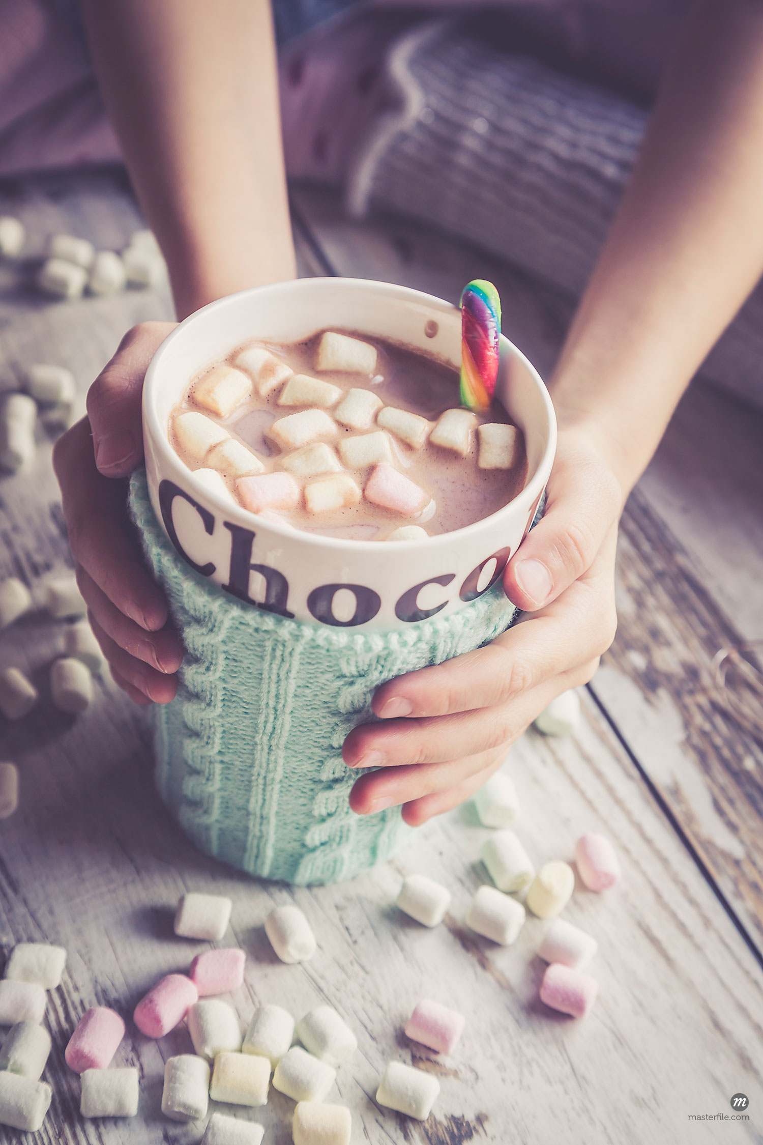 Hands cupping mug of hot chocolate and marshmallows, with knit mug warmer  © Masterfile