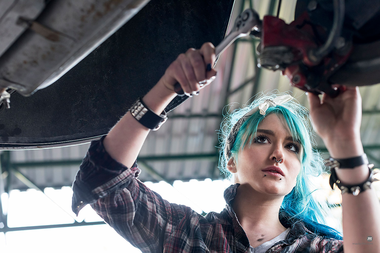 Young female mechanic with blue hair fixing car in auto repair shop  © Masterfile