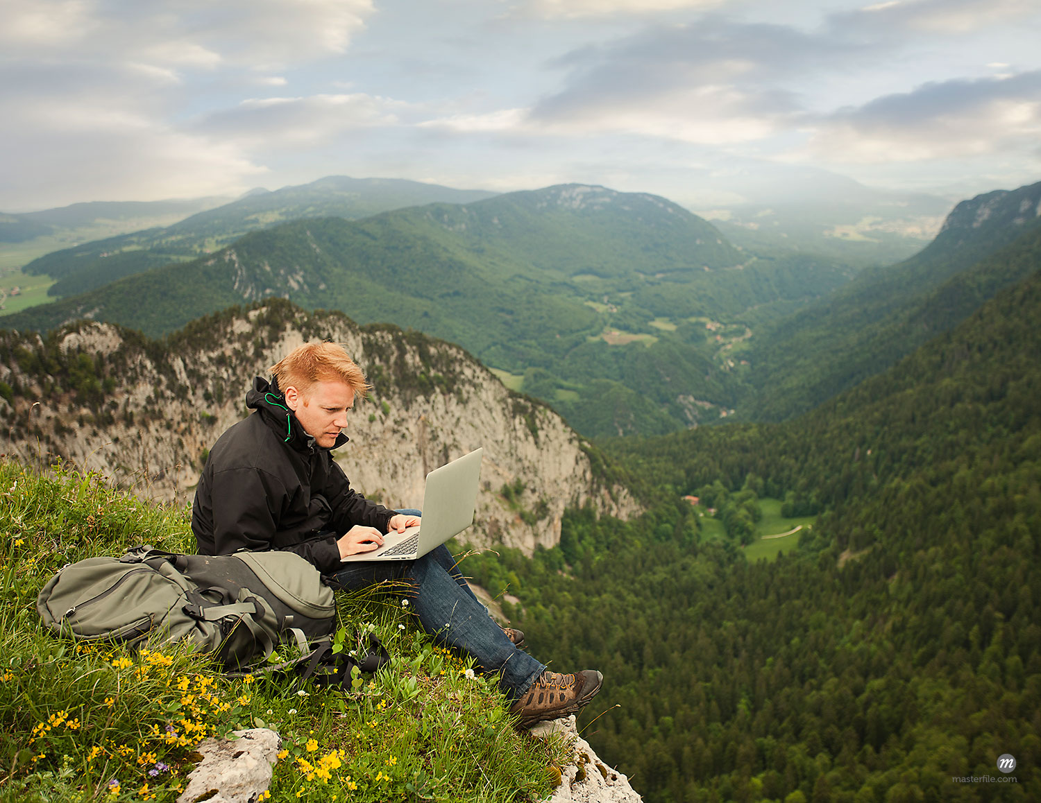 Caucasian man using laptop on remote cliff's edge  © Masterfile