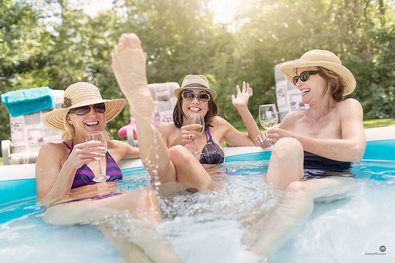 Three mature women sitting together in paddling pool drinking wine  © Masterfile