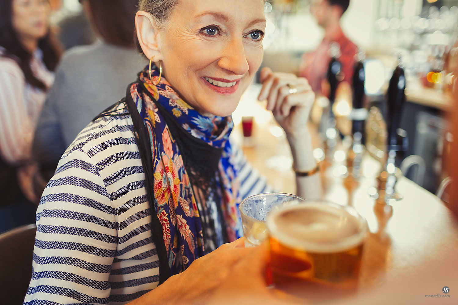 Senior woman drinking beer at pub  © Masterfile