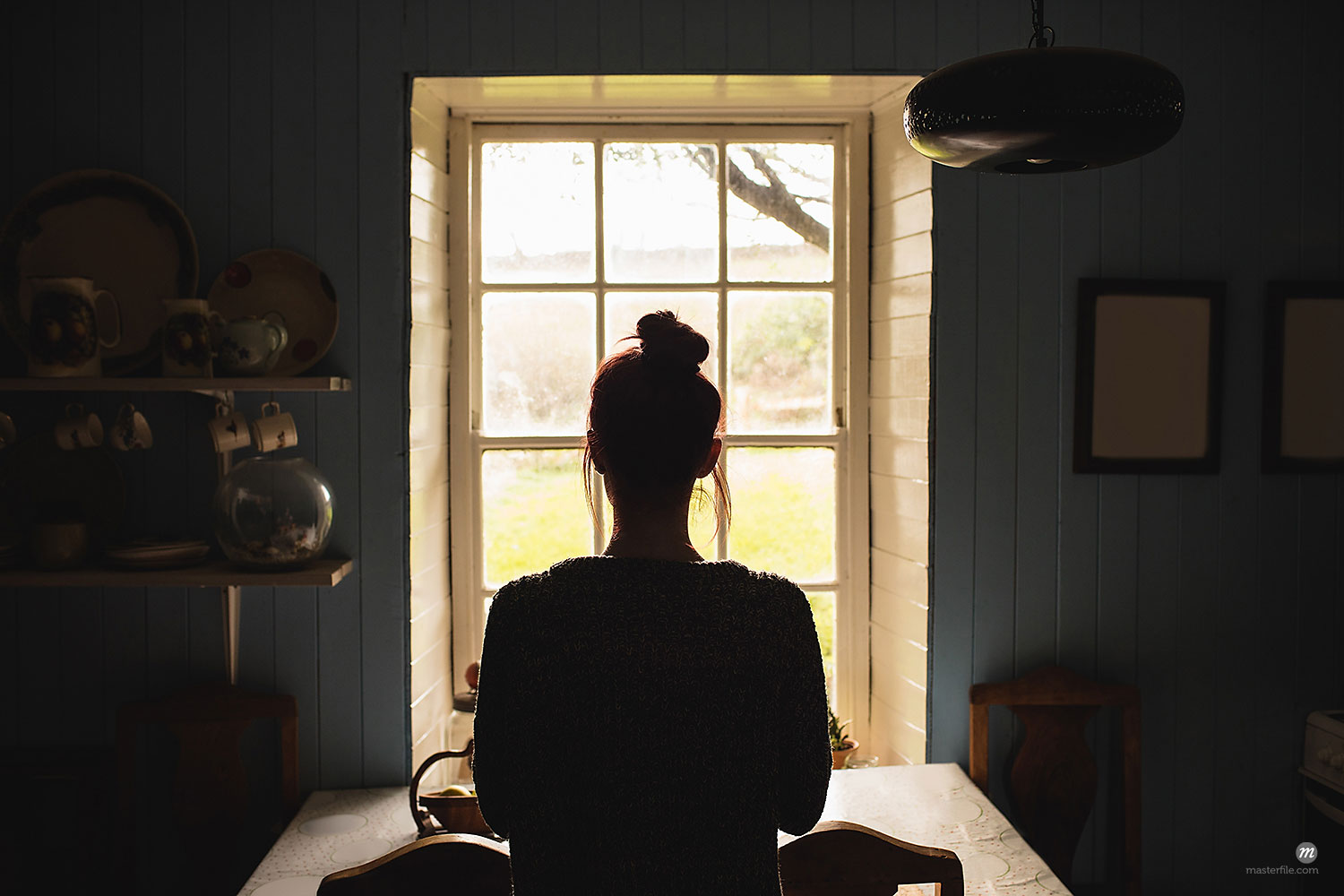 Woman silhouetted in front of window © Masterfile