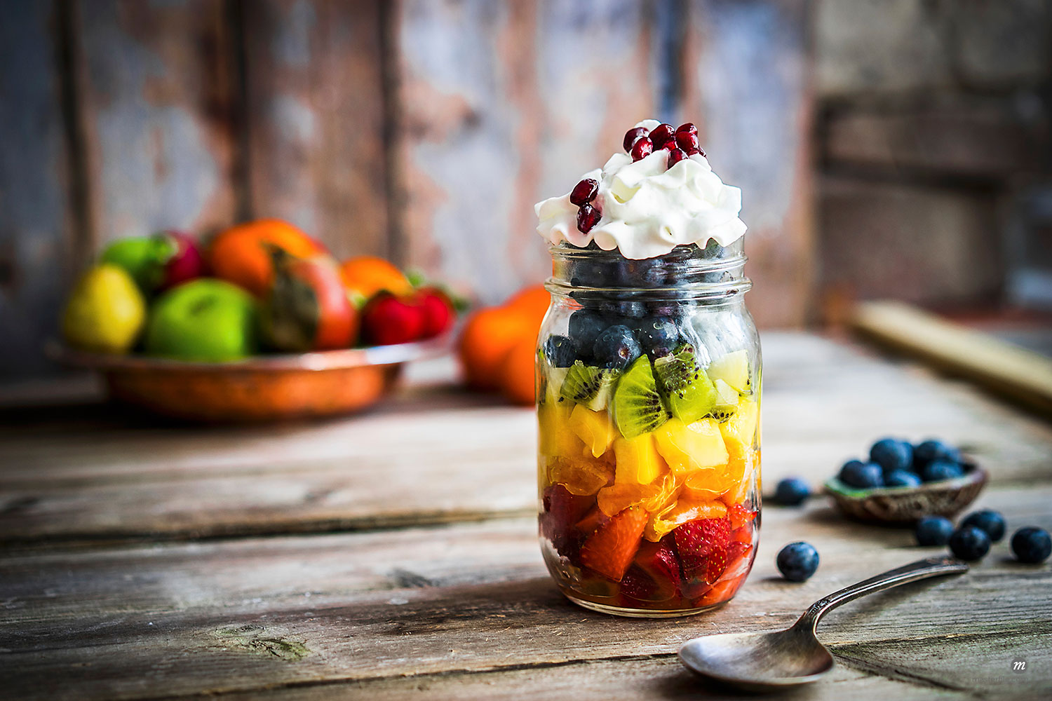 A rainbow fruit salad in a mason jar topped with cream and pomegranate seeds on rustic table  © Masterfile
