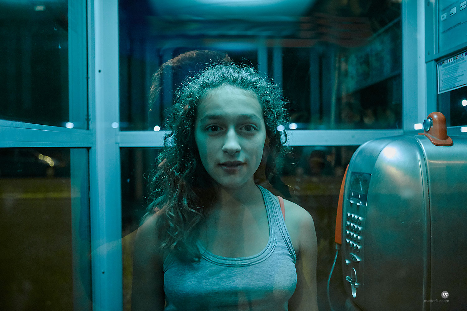 Portrait of teen girl standing in phone booth at night  © Masterfile