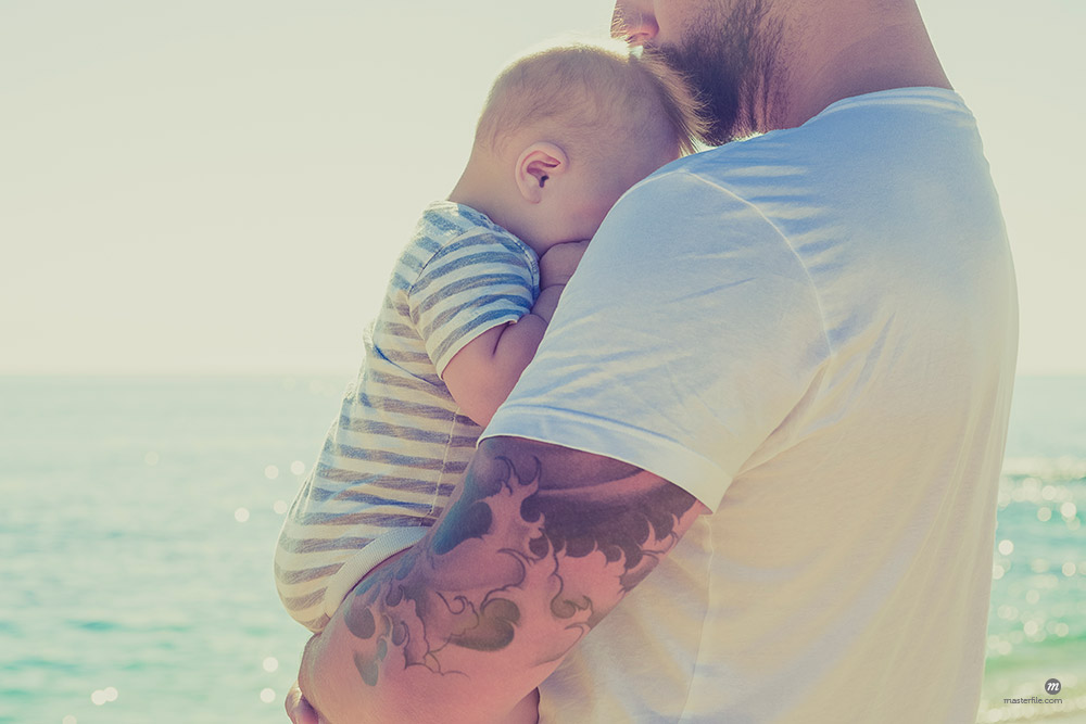 Close up of father holding baby son at beach © Masterfile