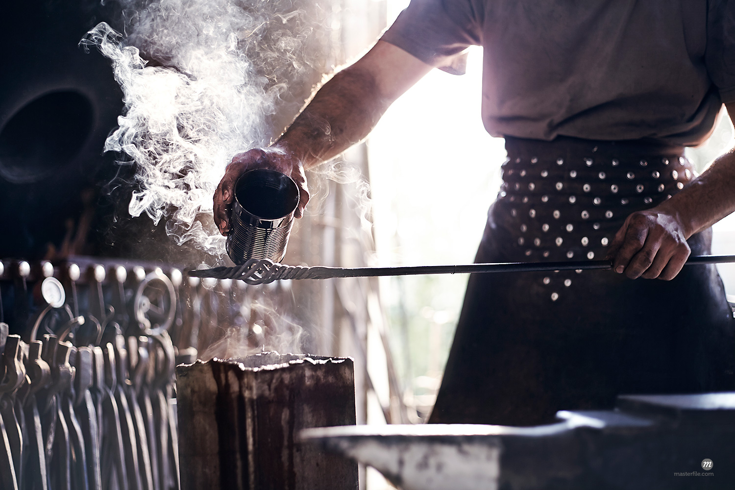 Blacksmith pouring hot liquid over wrought iron in forge  © Masterfile