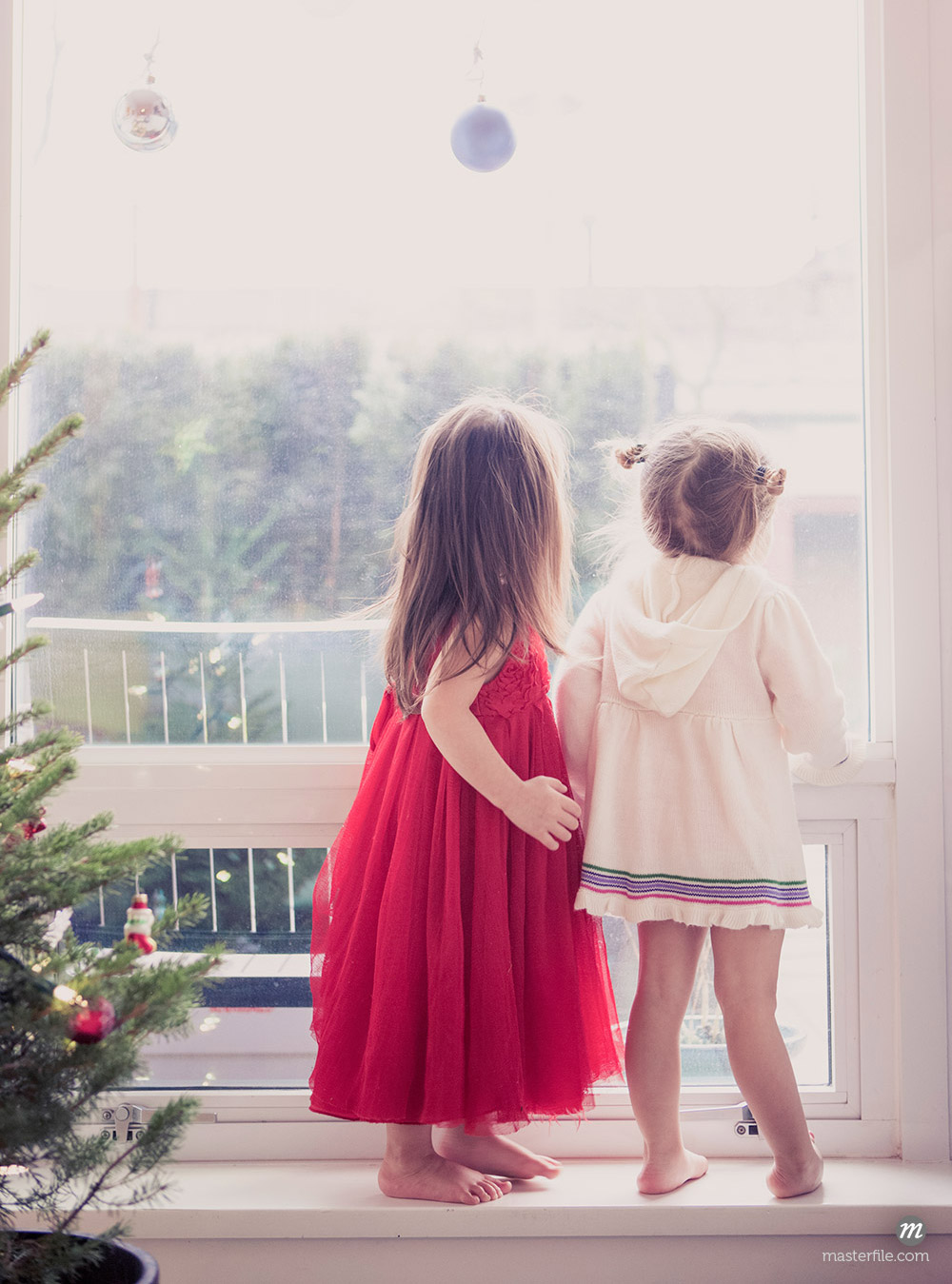 Girls on window ledge below Christmas ornaments © Masterfile