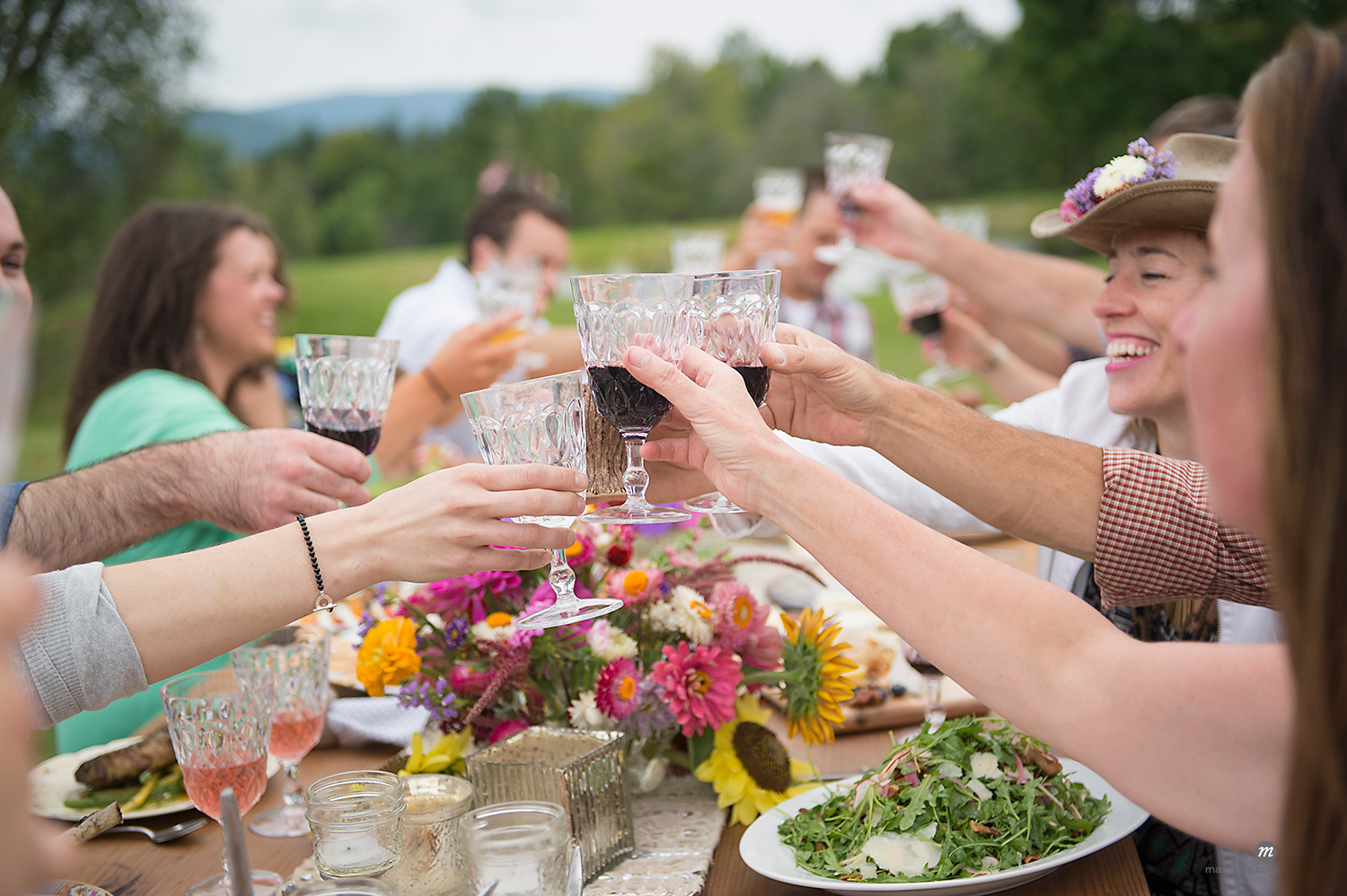 Family and friends making a toast at outdoor meal © Masterfile