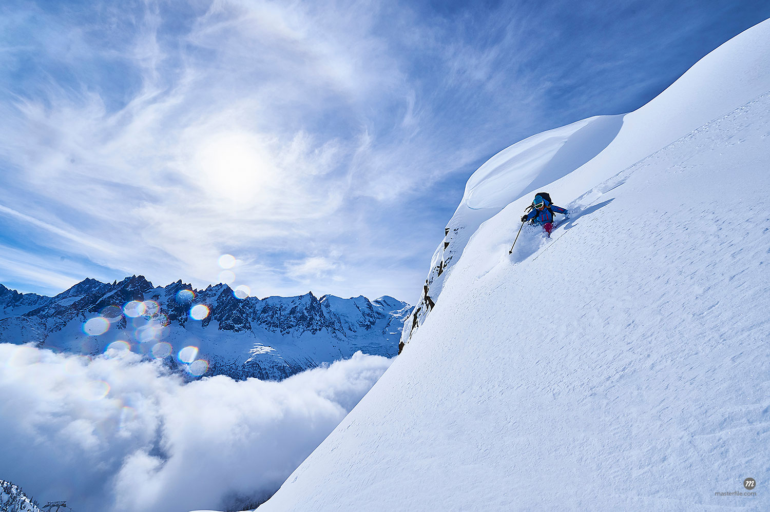 Woman skiing down steep mountainside in Swiss Alps, Gstaad, Switzerland © Masterfile