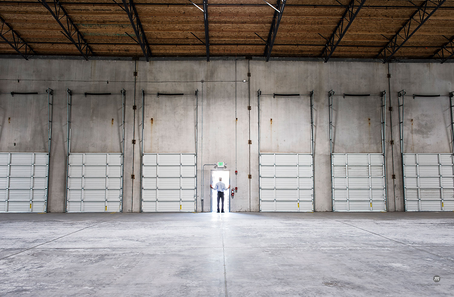 Man standing doorway of new warehouse waiting for the arrival of the fist truck with new business  © Masterfile