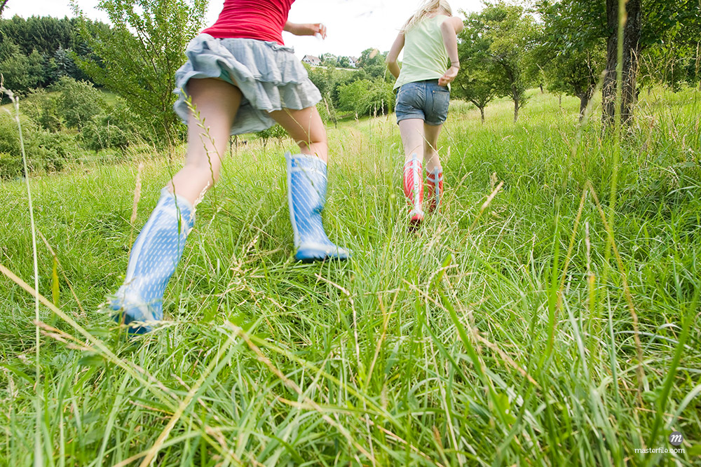 Two Girls Running in Field © Bettina Salomon / Masterfile