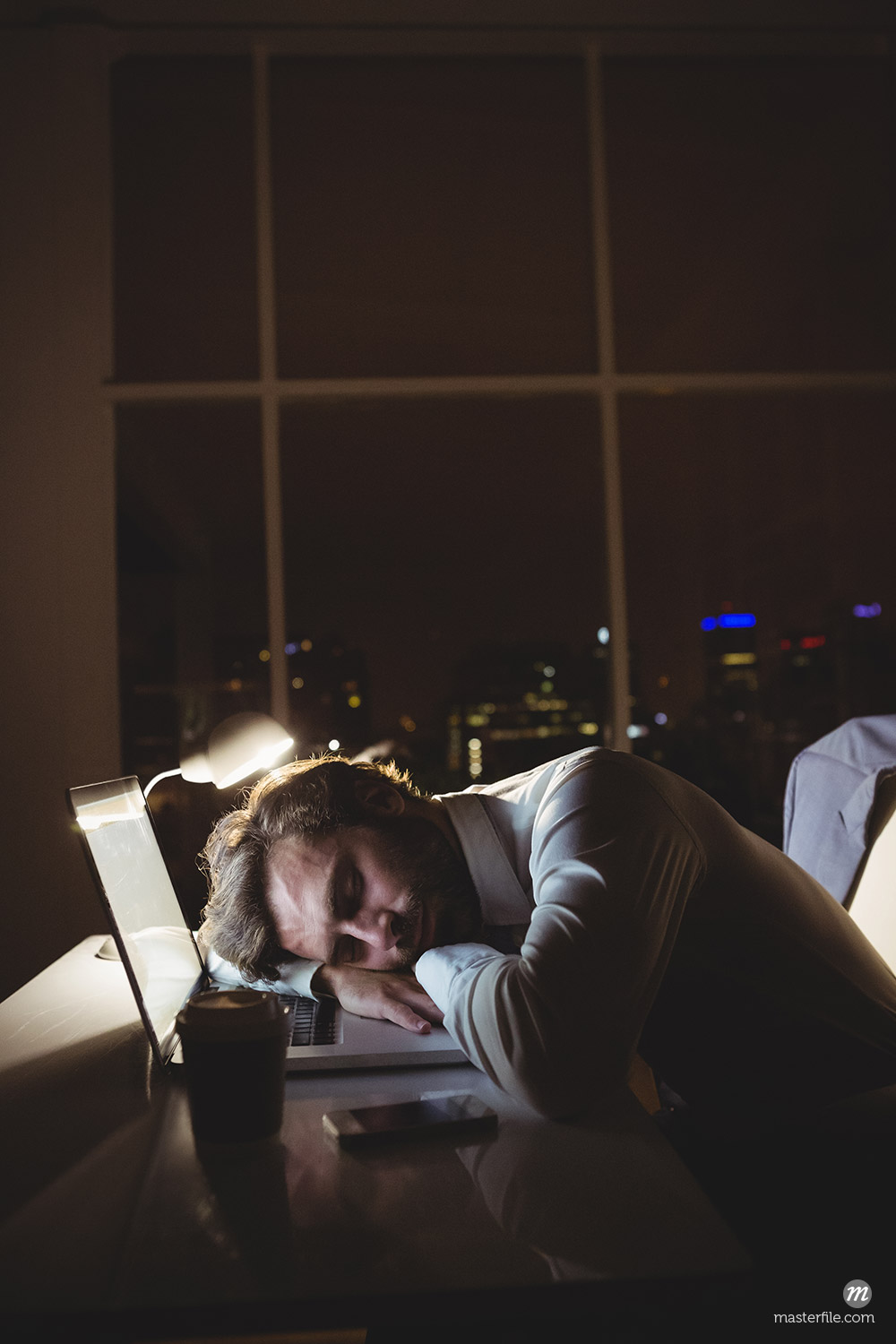 Businessman sleeping on his laptop at night © Masterfile