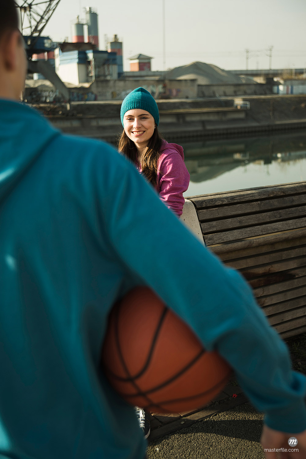 Teenage girl outdoors wearing toque, smiling and looking at teenage boy holding basketball, industrial area, Mannheim, Germany © Uwe Umstätter / Masterfile