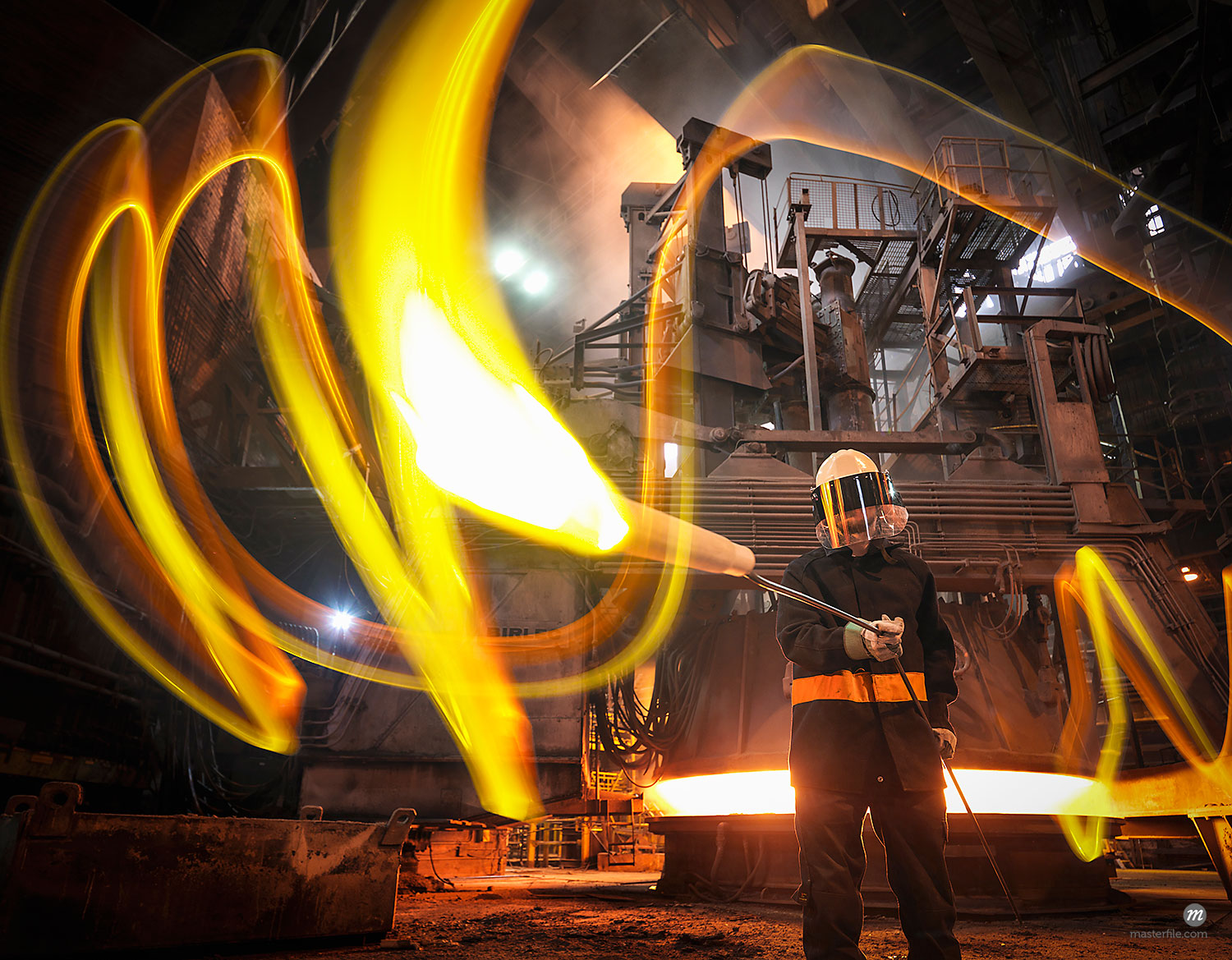 Steelworker with molten metal sample taken from furnace  © Masterfile
