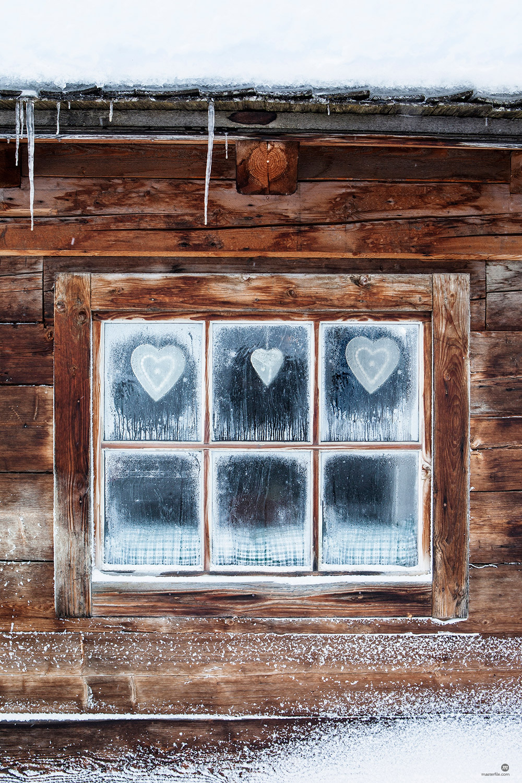 Hearts on window of log cabin © Masterfile