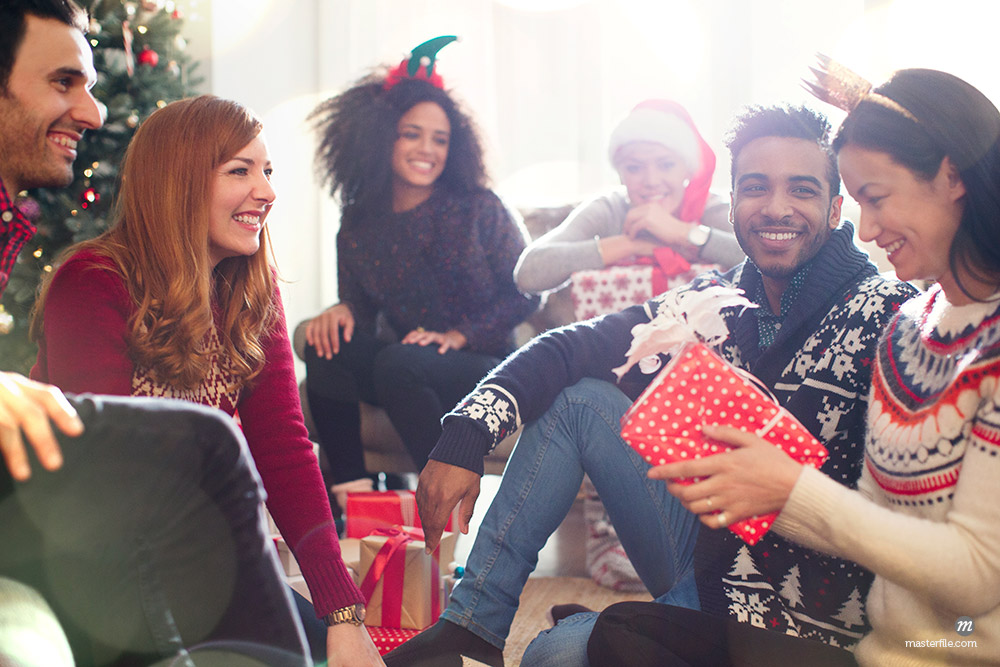 Friends opening Christmas gifts in living room © Masterfile