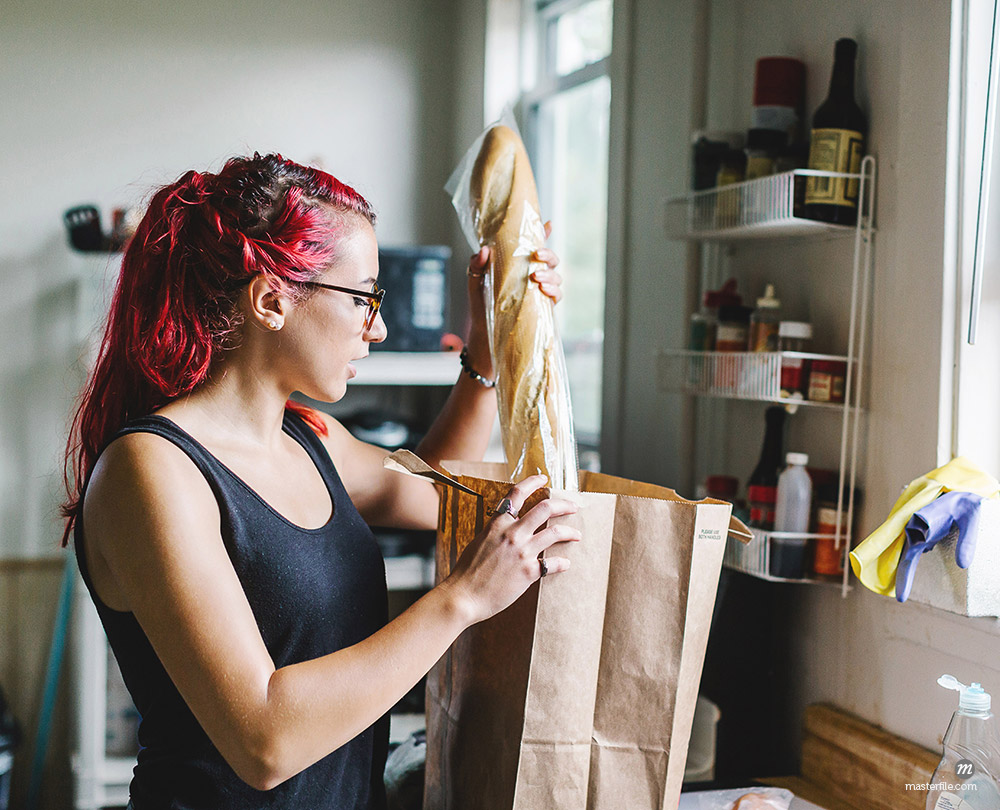 Young woman with pink hair unpacking baguette from shopping bag in kitchen © Masterfile