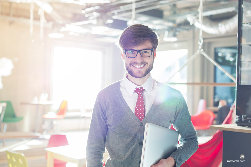Portrait of confident businessman holding laptop in sunny office © Masterfile
