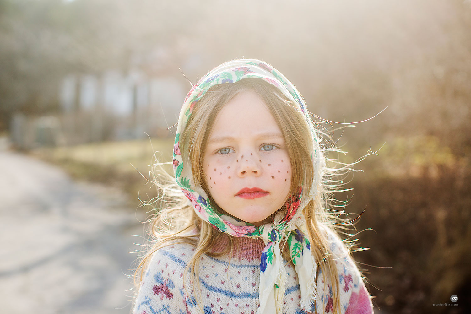 Portrait of girl dressed up as Easter witch wearing headscarf  © Masterfile