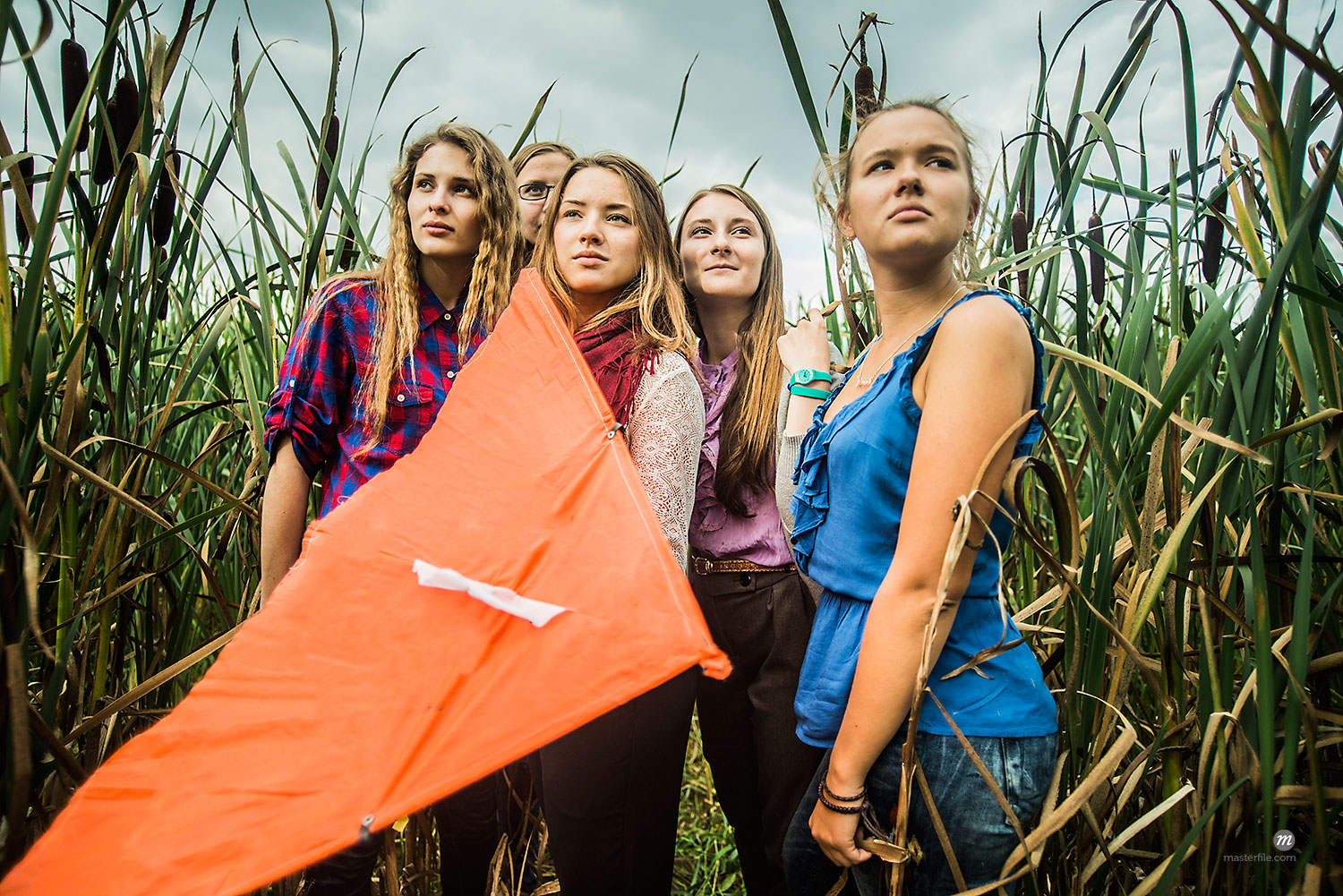 Portrait of five young women in marsh holding kite  © Masterfile