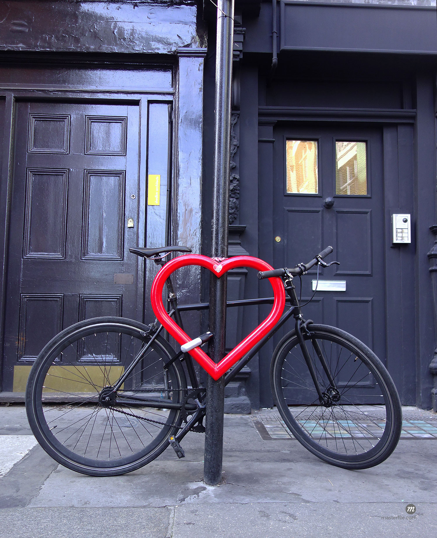 Bicycle secured with lock to heart-shaped post  © Masterfile