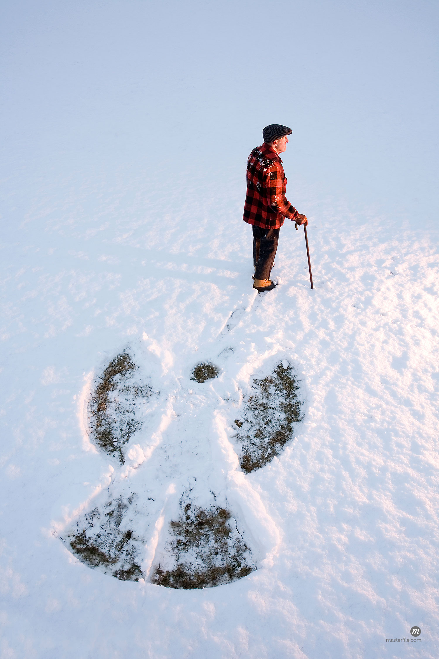 An elderly using a cane, standing in the snow beside a snow angel, New England, USA  © Michael Eudenbach / Masterfile.