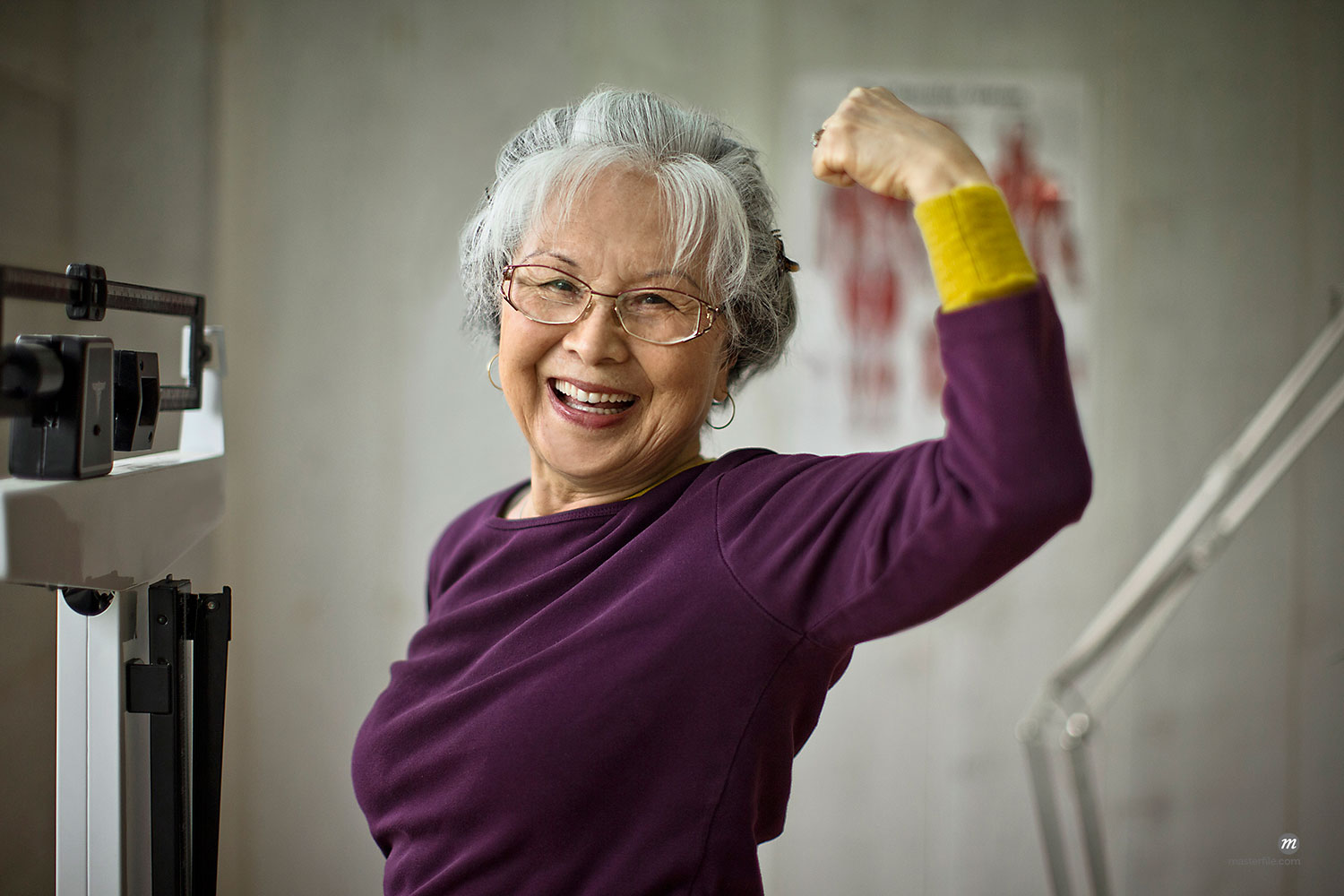 Smiling senior woman flexing her muscles while standing on scales  © Masterfile