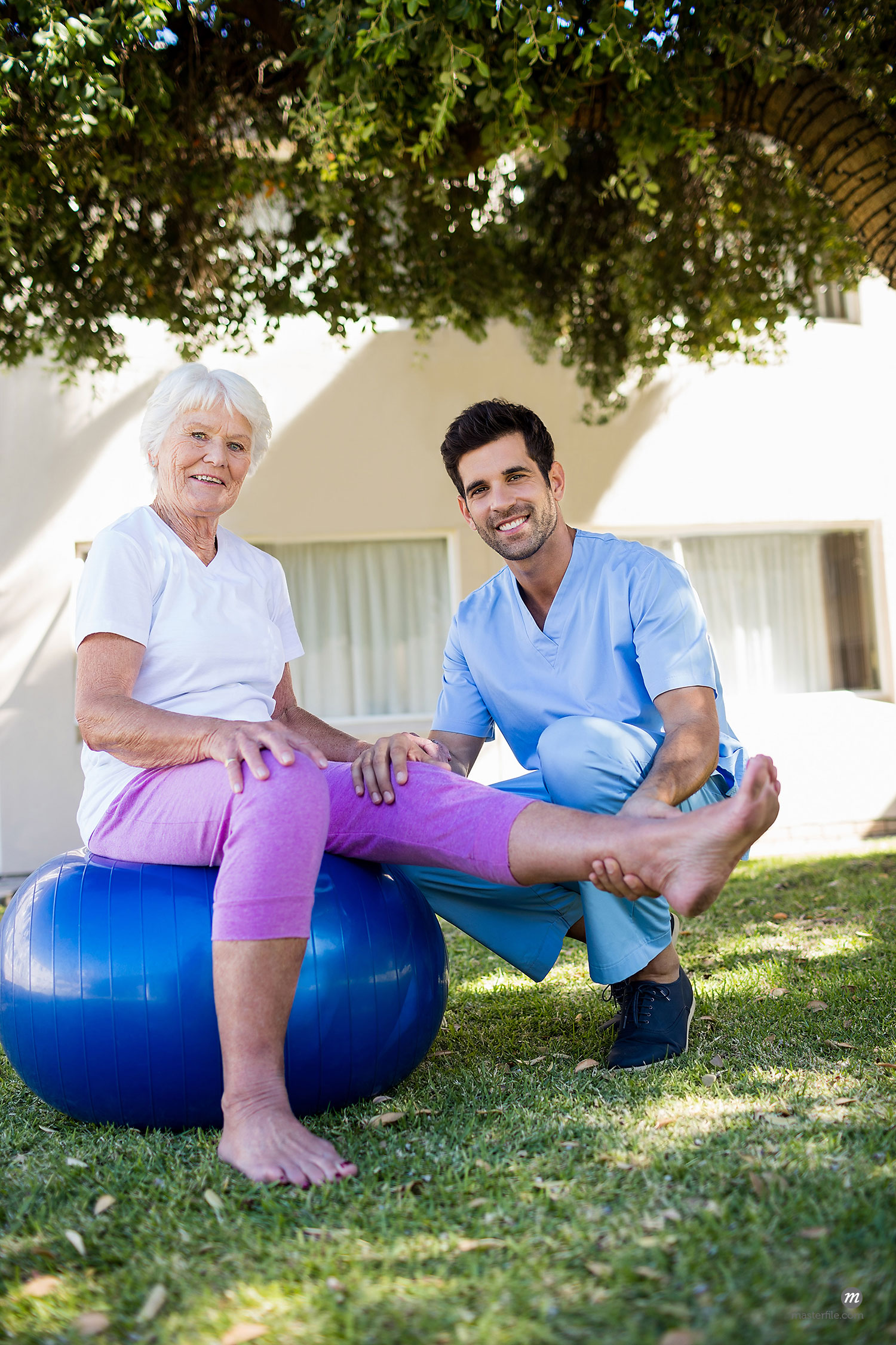 Nurse helping senior woman during exercises  © Masterfile