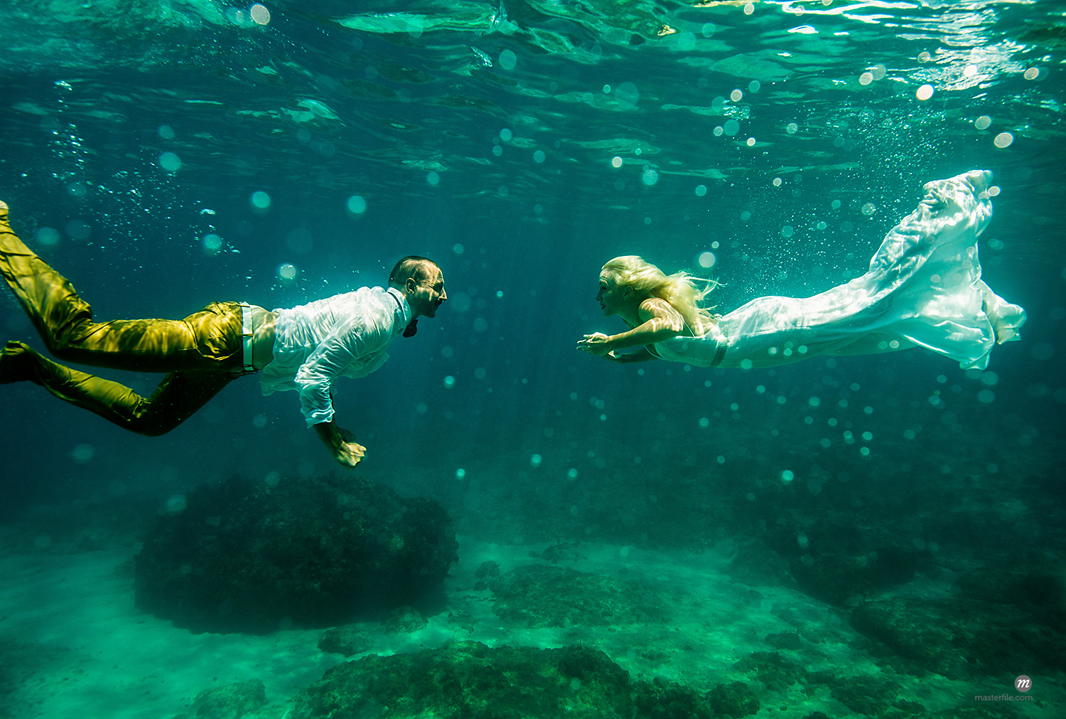 Couple in wedding attire, underwater, swimming towards each other  © Masterfile