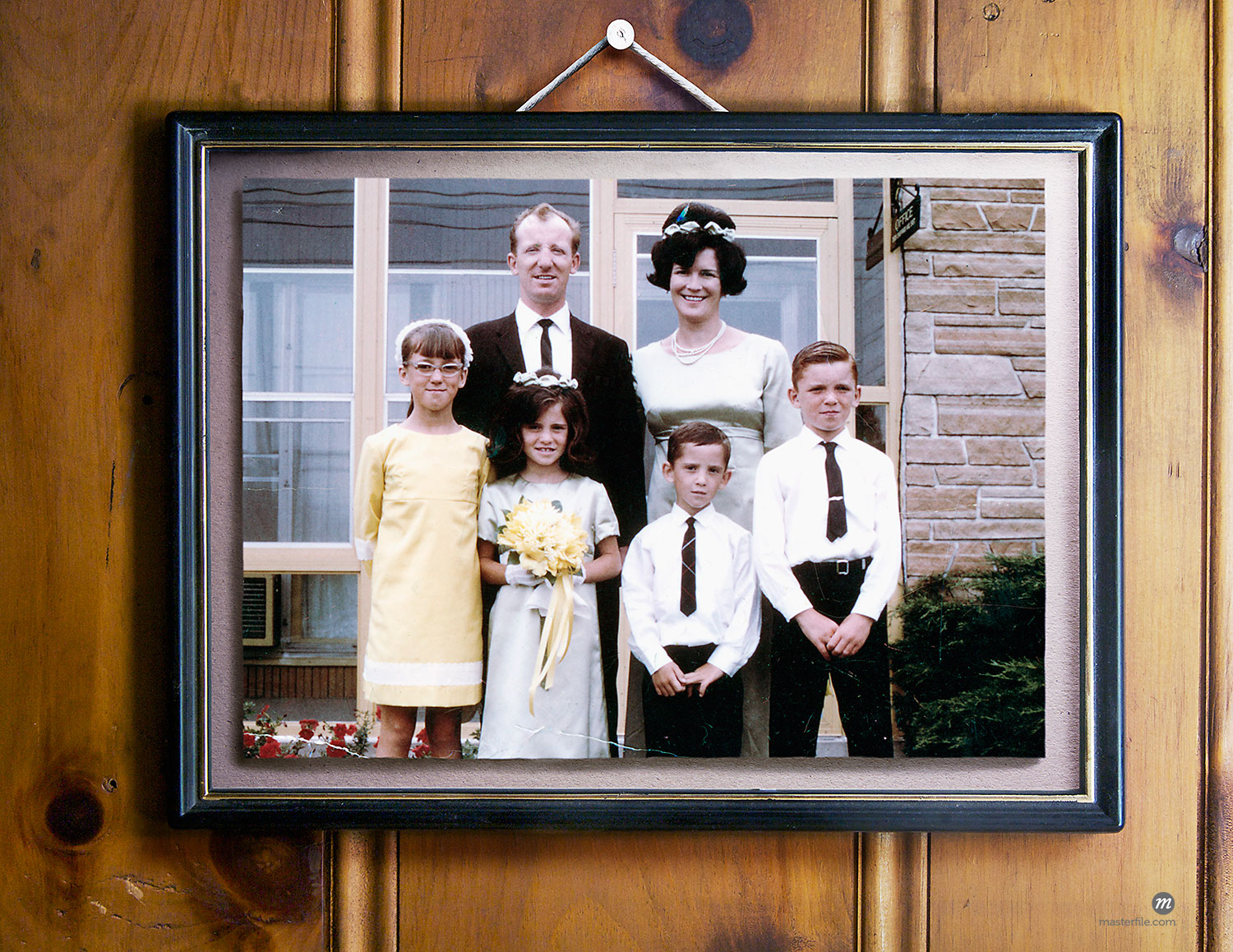 Vintage family portrait hanging on wall  @ Andrew Kolb / Masterfile