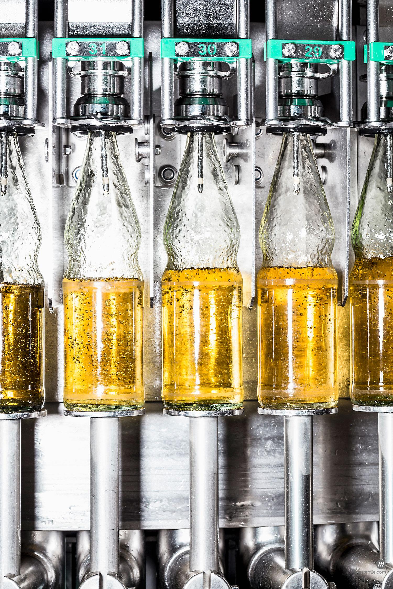 Close up of bottles on conveyor belt  © Masterfile