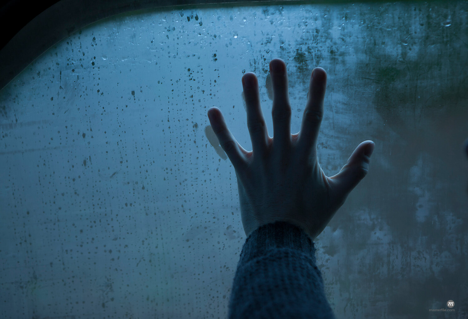 Hand on wet window © Nathan Jones
