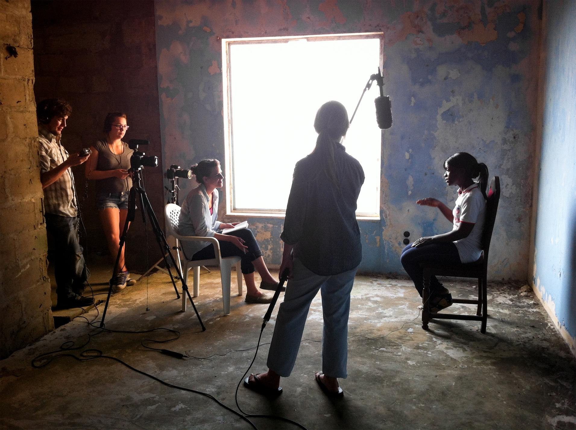 (L to R) Students Jim Tuttle, Kristina Subsara, Jessica Suarez and journalist Clair MacDougall interview Liberian journalist Tecee Boley in Monrovia, Liberia.