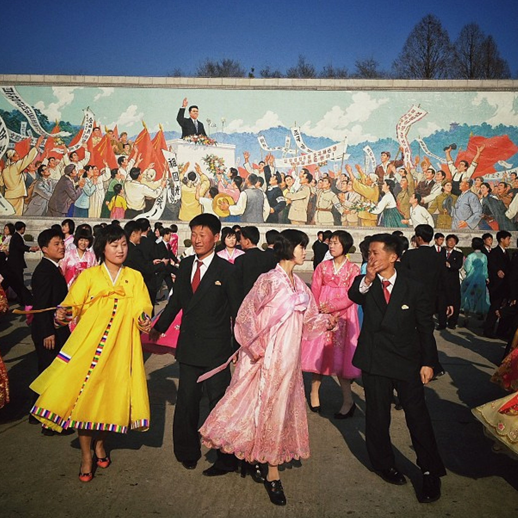 North Koreans dance a traditional folk dance together beneath a huge mosaic of the late leader  Kim Il Sung  in Pyongyang. Image courtesy of David Guttenfelder.