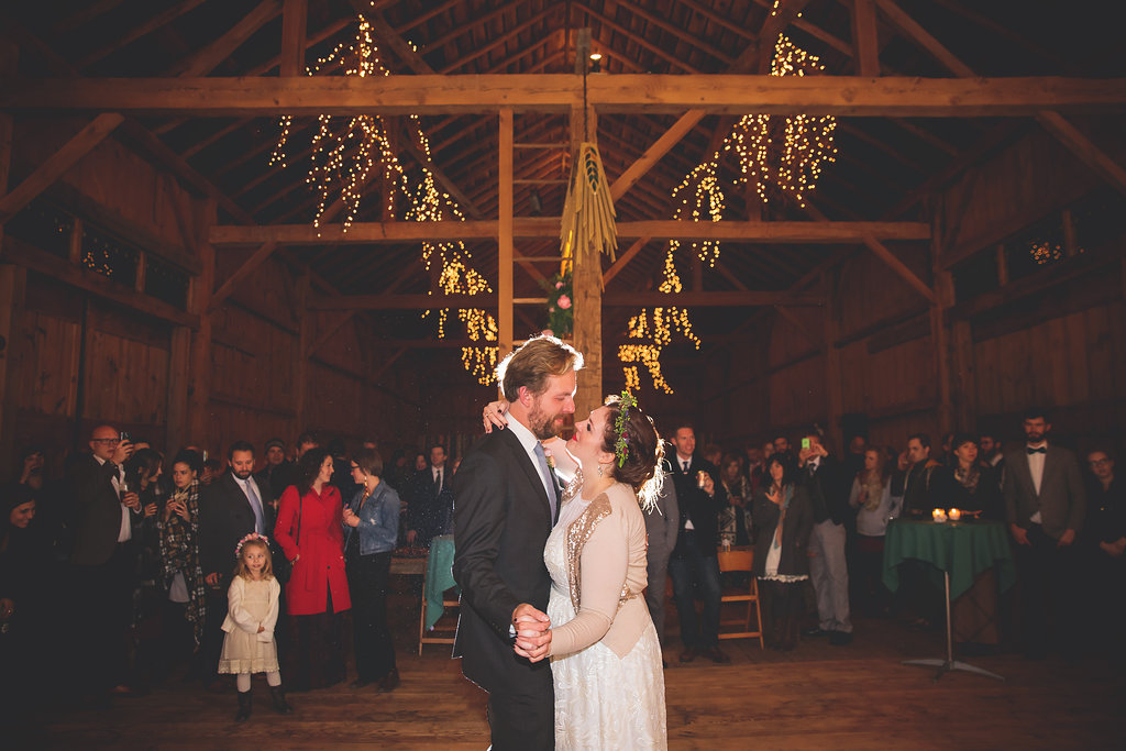 The high, open-beam ceilings of the barn are decorated with lit branches and hand-made chandeliers.   Image by  Mo Schultz Photography