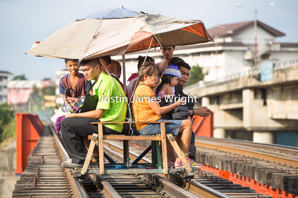Philippines National Railways (PNR), Sta. Mesa, City of Manila,   Passengers use a trolley, a mode of public transportation which runs on the railway tracks in between regular trains  Philippine Image: 4106  If you wish to purchase a photography print of this image, or would like to license this image please contact us using the form below.  Please kindly include the Image Title and Image Ref # in your message, we will get back to you.