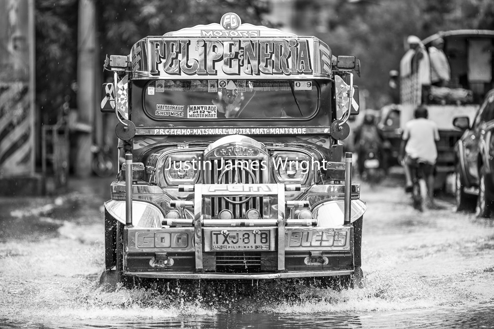 A Passenger Jeepney Navigates a Flooded Street during a Typhoon, Makati City, Metro Manila, Philippines   Philippine Image # 4109  If you wish to purchase a photography print of this image, or would like to license this image please contact us using the form below.  Please kindly include the Image Title and Image Ref # in your message, we will get back to you.