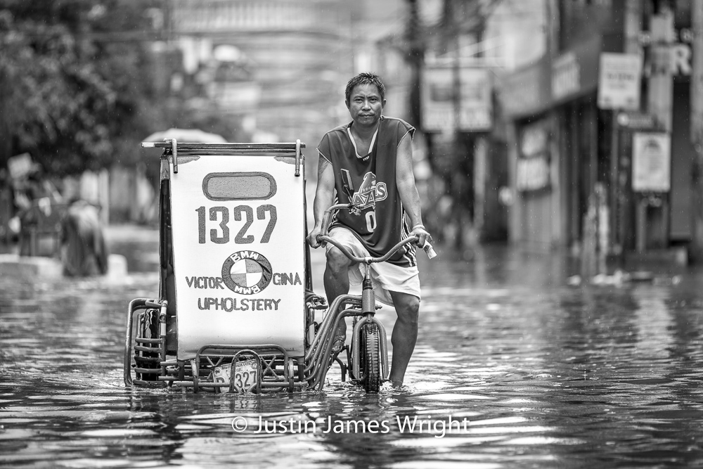 A Pedicab Navigates a Flooded Street, Makati City, Philippines