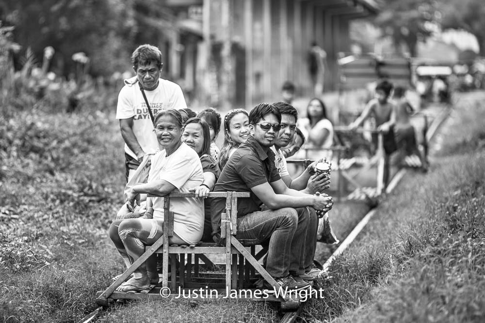 Commuters depart Alabang railway station on board a trolley   Homemade wooden carts take Filipinos to work or school without the hassles of traffic and at a cheaper price. These improvised carts ply the same railway tracks used by the trains of the PNR Metro Commuter Line. As soon as the train rumbles past, the men heave their homemade carts back onto the tracks and passengers hop aboard.  Alabang, Muntinlupa, Philippines.  Canon EOS Mk III, EF 135 mm, F 2.0, 1/400 sec.