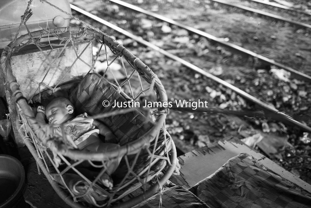 A baby sleeps next to the railway tracks   Sta Mesa, Manila, Philippines.  Canon EOS Mk III, EF 35 mm, F 1.4, 1/160 sec.