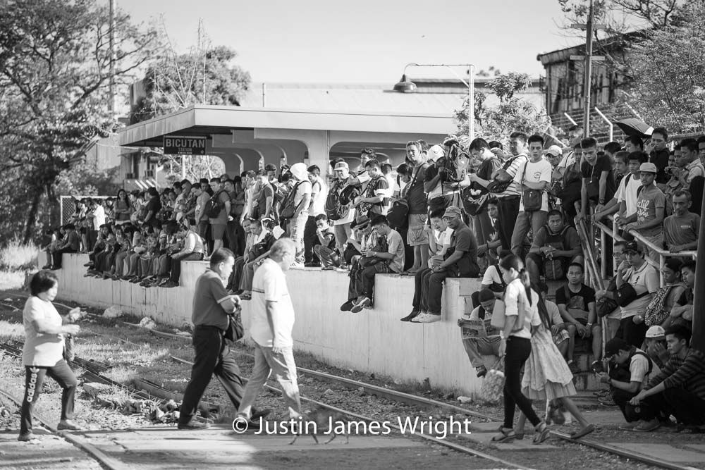 Commuters waiting for a train at Bicutan station   Makati City, Metro Manila, Philippines.  Canon EOS Mk III, EF 70 - 200 mm, F 4.0, 1/640 sec.