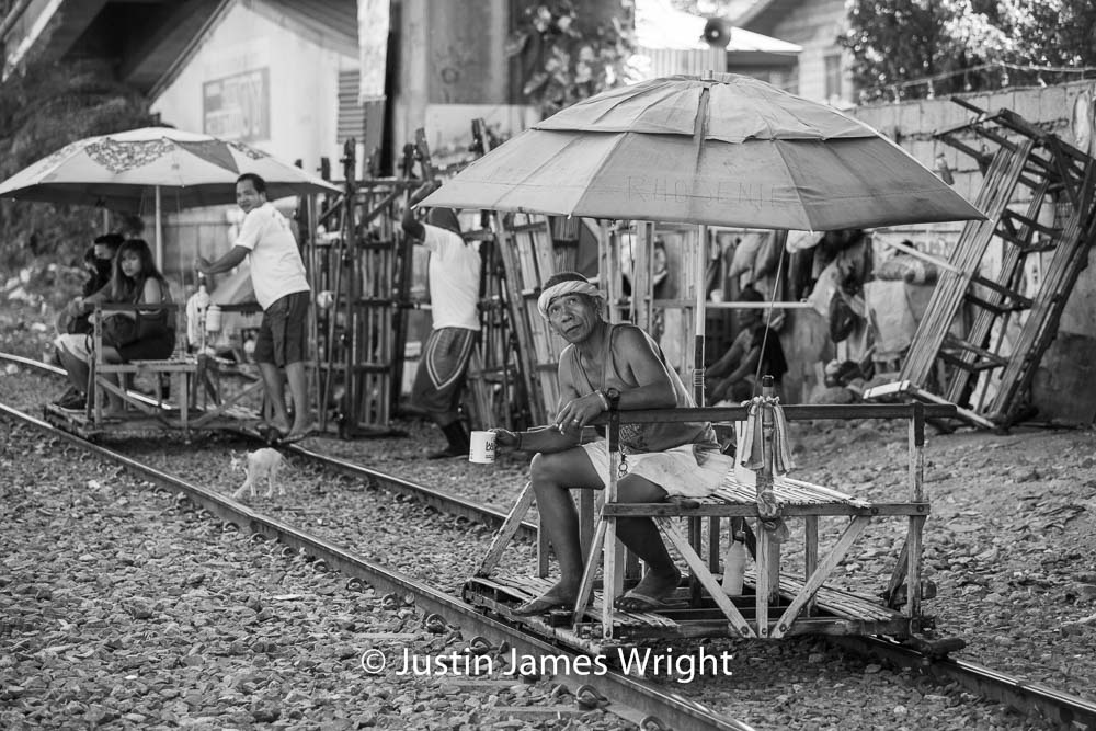 A trolley operator takes an early morning coffee break, while waiting for passengers   Pandacan, Manila, Philippines.  Canon EOS Mk III, EF 70 - 200 mm, F 4.0, 1/500 sec.