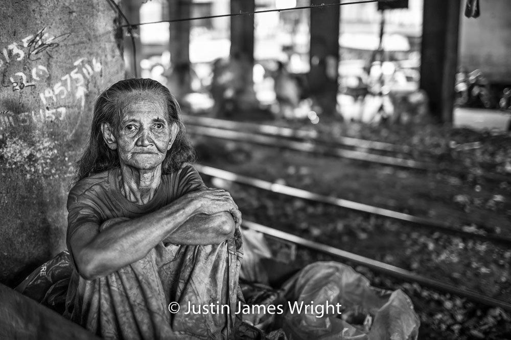 A portrait of a Filipina   This dear lady lives here, under a flyover and next to the railway tracks.  Sta Mesa, Manila, Philippines.  Canon EOS Mk III, EF 35 mm, F 1.4, 1/80 sec.