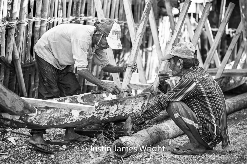 The Boat Builder   Mang Alog enacts the art of crafting a  banca  to a captive audience of one; tobacco-chewing Mang Aleo.  Resilience - The Isla Pulo Community, Philippines.  January 2013. Canon EOS Mk III, EF 100 mm, F 2.8, 1/400 sec.
